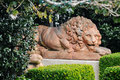 Lion statue in formal garden shot of a surrounded by well manicured greenery Stock Images