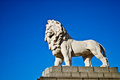 Lion statue imposing guarding the south bank of the thames river near the london eye ferris wheel attraction in london Royalty Free Stock Image