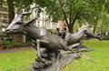 Lioness chasing lesser kudu a statue of a down a in lower grosvenor park london Royalty Free Stock Image
