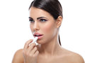 Lips care woman applying balsam on Royalty Free Stock Images