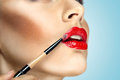 Lips like magnet fashion photo of face makeup demonstrating of a cute girl painted with bright lipstick with the hepl of brush Stock Photo