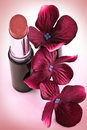 Lipstick and crimson flowers a new next to colored silk Royalty Free Stock Photos