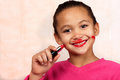 Lipstick girl a smiling young applies in an unconventional manner Royalty Free Stock Photography