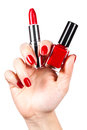 Lipstick and nail polish in a hand Royalty Free Stock Photo