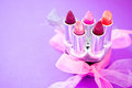 Lipsticks and lipglosses with bow Royalty Free Stock Images