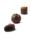 Liqueur chocolates iv brightly lit dark against a white background copy space Stock Photos