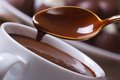 Liquid chocolate dripping from the spoon in a cup closeup horizontal macro Royalty Free Stock Photography