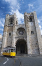 Lisbon cathedral and a tramway typical s yellow tram passes the se patriarcal in portugal this was built on the site of an Royalty Free Stock Photos