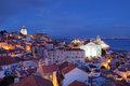 Lisbon portugal twilight view over alfama quarter of as seen from the miradouro de santa lucia with st stephen church igreja de Royalty Free Stock Image