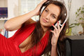 Listen to music listening young woman with headset in a cluttered room Royalty Free Stock Images