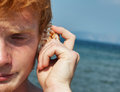 Listen to seashell young boy listening sea shell Royalty Free Stock Photography