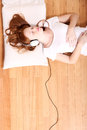 Listening music a young redhead girl lying on the floor while Royalty Free Stock Photos