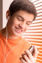 Listening to favourite music cheerful teenage boy in headphones the and smiling Royalty Free Stock Photos