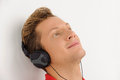 Listening to the favourite music close up of cheerful young man in headphones Stock Photography