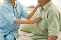 Listening to heartbeat doctor of senior patient at home Royalty Free Stock Images