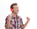 Listening to his favourite music happy young man in headphones the and gesturing while isolated on white Stock Image