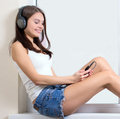 Listening to the music beautiful young woman while sitting on windowsill Stock Photos