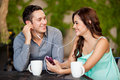 Listening to music on a date happy hispanic couple some while having coffee Royalty Free Stock Image