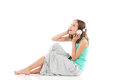 Listening to the music ecstatic young girl with headphones is sitting on floor and full length studio shot isolated on white Royalty Free Stock Images