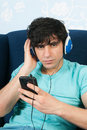 Listening to music with the smart phone young man sitting in living is Royalty Free Stock Photography
