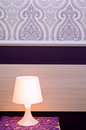 Lit bedside lamp a with violet theme decorative wallpaper Stock Images