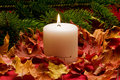 Lit candle sitting in dried maple leaves Royalty Free Stock Image