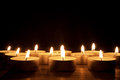 Lit candles rows of in the dark Royalty Free Stock Photography