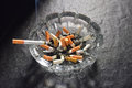 Lit cigarette with smoke lying on an ashtray Royalty Free Stock Photo