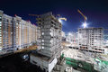 Lit high multi storey buildings under construction and cranes at dark night Stock Photos