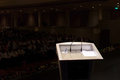 Lit rostrum in front of darkened function hall Royalty Free Stock Photo