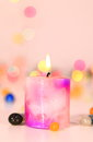 A lit up candle with bokeh background candlet and multicolour stones Royalty Free Stock Image