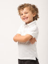 Litle boy standing with his arms crossed Stock Image