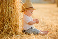 Little adorable baby boy with big brown eyes in a hat sits in a Royalty Free Stock Photo