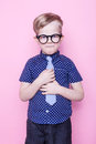 Little adorable boy in tie and glasses. School. Preschool. Fashion. Studio portrait over pink background Royalty Free Stock Photo