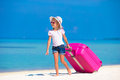 Little adorable girl with big bag on white beach Royalty Free Stock Photo
