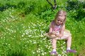 Little adorable girl on flower green glade Royalty Free Stock Photo
