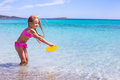 Little adorable girl playing frisbee during on a tropical white beach Stock Photography