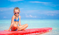Little adorable girl on surfboard in turquoise sea yoga position meditating Stock Photography