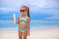 Little adorable girl in swimsuit holds suntan lotion bottle this image has attached release Stock Photos