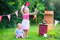 Little adorable kids playing with toy kitchen in the garden Royalty Free Stock Photo