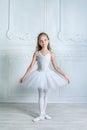 A little adorable young ballerina isposing on camera in the inte interior studio Royalty Free Stock Photos