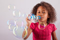 Little african asian girl blowing soap bubbles cute american Stock Images