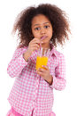 Little african asian girl drinking orange juice isolated white background Royalty Free Stock Image
