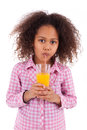 Little african asian girl drinking orange juice isolated white background Stock Photos