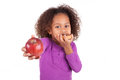 Little african asian girl eating a chocolate cake and holding an apple isolated on white background Royalty Free Stock Photo