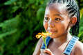 Little african girl blowing at flower.