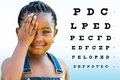 Little african girl testing eyesight close up portrait of with braided hairstyle closing on eye with hand vision chart with Royalty Free Stock Image