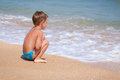Little alone boy sitting on the beach near water Royalty Free Stock Photo