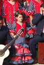 Little andalusian wearing a traditional dress nerja spain october girl red is standing between two musicians on october in nerja Stock Photos