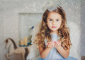 Little angel in light blue dress blowing snow Royalty Free Stock Photo